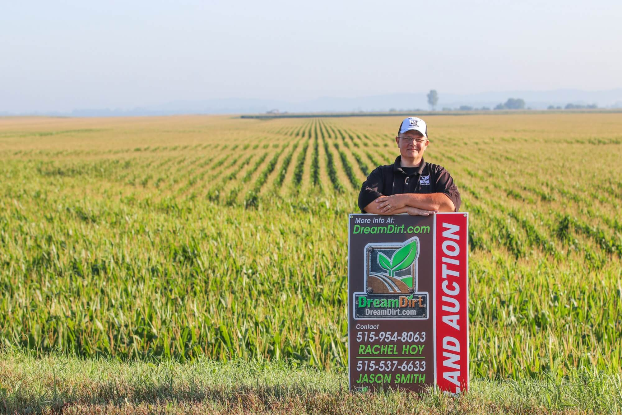 A DreamDirt auctioneer poses in a field with a Land Auction sign