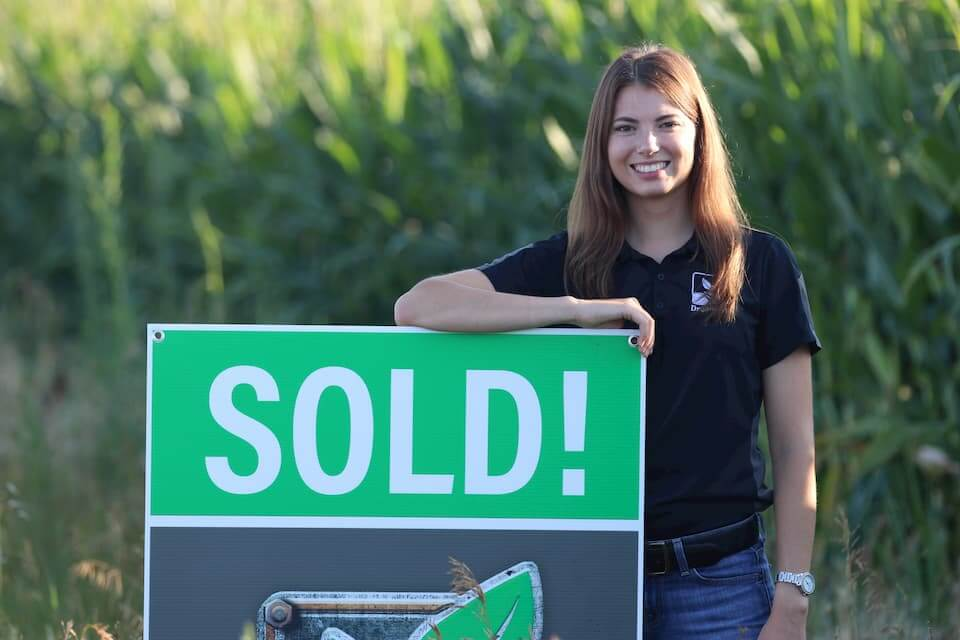 A DreamDirt representative poses with a Sold sign