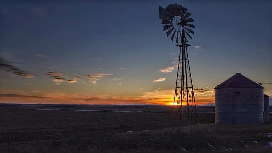 Photo of a windmill with sun setting in the background.