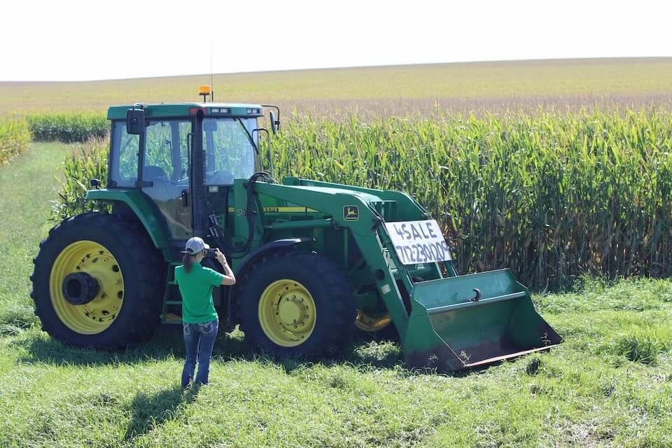 A DreamDirt representative takes pictures of a tractor for sale.