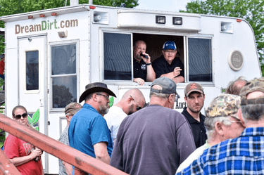 DreamDirt auctioneers call out from a DreamDirt RV.