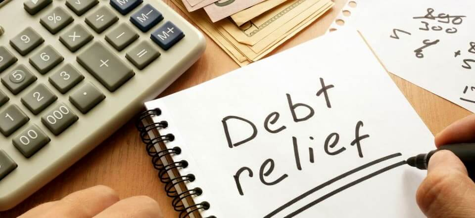 """The words """"Debt Relief"""" are written on a notepad."""