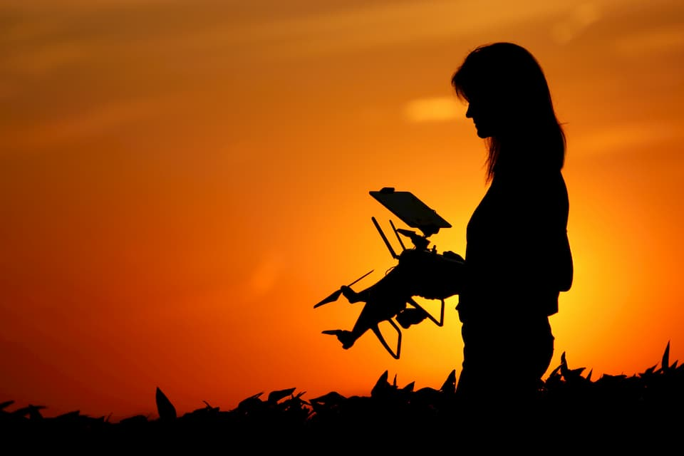 A female auctioneer's silhouette holding a drone as the sun sets in the background.