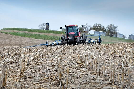 Photo of an oncoming tractor pulling farm equipment over a field.