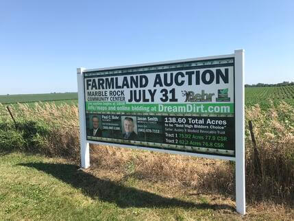 A photo of an in-person auction advertisement on the side of the road.