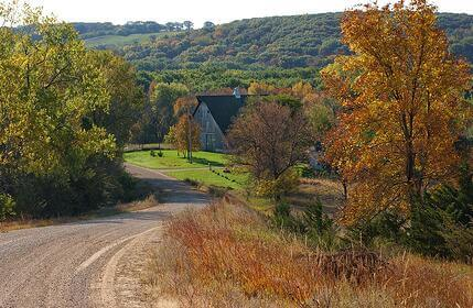 Scenic photo of a gravel road leading to a farm property.